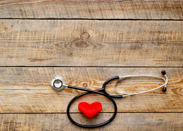 new stethoscope with red plush heart on  wooden table  isolated close up